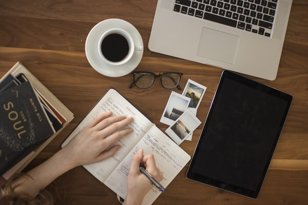 Image of someone writing in a notebook at a desk