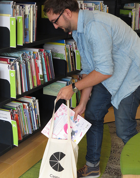 librarian adding books to bag