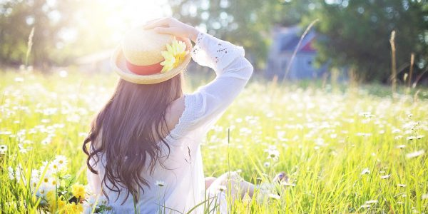 woman holding her hat sitting in a meadow in sunlight